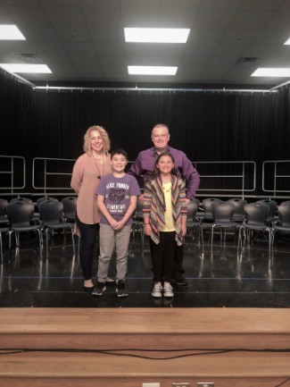 2 adults, 2 children standing on school stage
